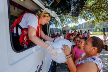 September 8, 2017. Houston, Texas. Red Cross volunteer Katie Bossc gives lunch to Jessica Guzma from an Emergency Response Vehicle at an apartment complex in Houston, Texas, in which over 200 ground floor units had water damage from Hurricane Harvey. Photo by Chuck Haupt for the American Red Cross